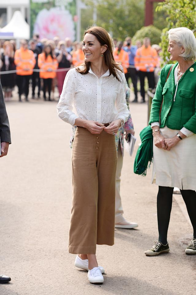 <p>The Duchess of Sussex chose a casual ensemble to unveil her 'Back to Nature' garden ahead of the Chelsea Flower Show. Dressed for the great outdoors, the mother-of-three wore a broderie anglaise shirt by M.i.h Jeans with Massimo Dutti camel-hued trousers and her go-to Superga 2750 Cotu trainers. <em>[Photo: Getty]</em> </p>