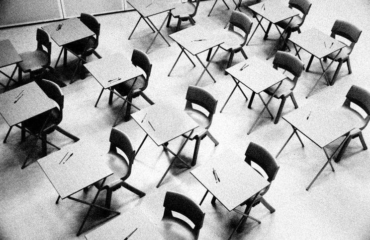 Unoccupied school desks in a classroom.
