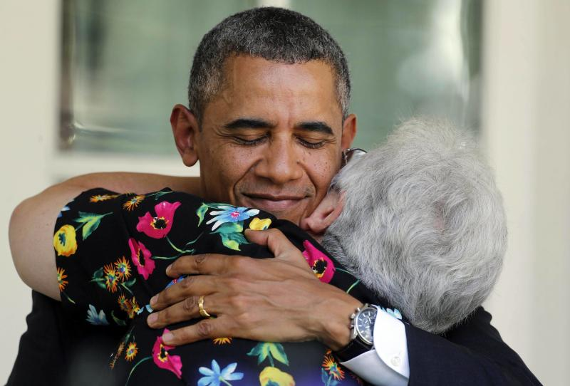 U.S. President Barack Obama hugs a woman after he speaks about the Affordable Care Act in the Rose Garden at the White House in Washington