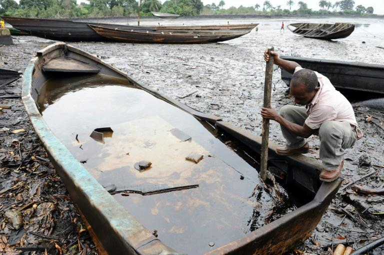 An man in Bodo, in the Ogoniland region, uses a stick to try to dig out crude oil from his boat. Local people said the oil spills devastated their livelihoods (2011 file picture)