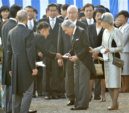 Japanese lawmaker Yamamoto hands a letter to Emperor Akihito during the annual autumn garden party at the Akasaka Palace imperial garden in Tokyo