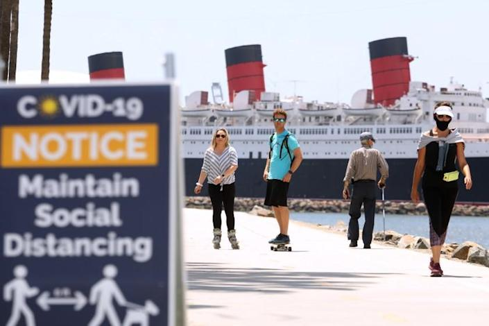 """LONG BEACH, CA - MAY 11, 2020 - - Scially distanced bikers and walkers, against a backdrop of the Queen Mary, make their way along pedestrian and beach bike path on the first day that Long Beach reopened the path on Monday May 11, 2020. The city of Long Beach eased a few of its public health restrictions, allowing under certain guidelines the reopening of pedestrian and beach bike paths, tennis centers and courts. Beach bathrooms are also reopening, but the parking lots and beaches still remain closed. (Genaro Molina / Los Angeles Times) <span class=""""copyright"""">(Genaro Molina/Genaro Molina/Los Angeles Times)</span>"""