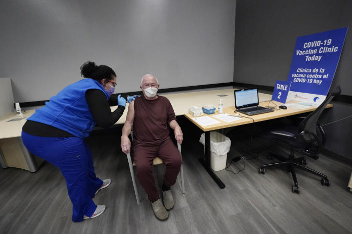"""Nurse Maria Maldonado administers a COVID-19 vaccine to 82-year-old David Evans, who had the recently opened vaccination site in Chelsea, Mass., Feb. 10, 2021, mostly to himself. """"That went pretty smoothly,"""" he remarked after. """"I was preparing for this to be an ordeal after hearing about places where people couldn't get appointments or they didn't have shots."""" (AP Photo/Elise Amendola)"""