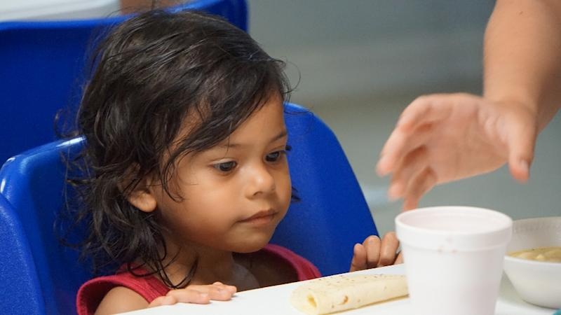 A young girl looks at a cup of soup handed to her by volunteers in a migration center in the border town of McAllen, Texas (AFP Photo/Gianrigo Marletta)