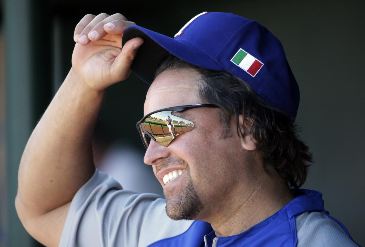 "FILE - In this March 6, 2013 file photo, Italy hitting coach and former Major League Baseball catcher Mike Piazza adjusts his hat during an exhibition spring training baseball game against the Los Angeles Angels in Tempe, Ariz. Piazza will be taking center stage with the Miami City Ballet. The Miami Beach-based dance company has tapped Piazza to play the role of a gangster in the May 3 production of ""Slaughter on Tenth Avenue."" (AP Photo/Morry Gash, File)"