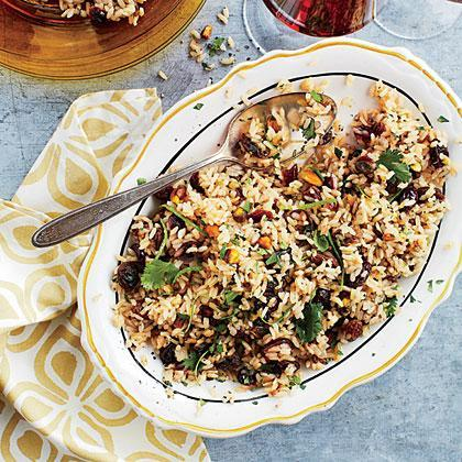 """<p>Skip the boxed <a href=""""https://www.myrecipes.com/ingredients/recipes-that-start-with-rice"""" rel=""""nofollow noopener"""" target=""""_blank"""" data-ylk=""""slk:rice mixes"""" class=""""link rapid-noclick-resp"""">rice mixes</a> and opt for this delicious homemade pilaf featuring dried cranberries, raisins, and pistachios, plus fresh herbs and spices. The sweetness of the dried fruit and the saltiness of the pistachios makes for the ultimate sophisticated side dish. </p>"""