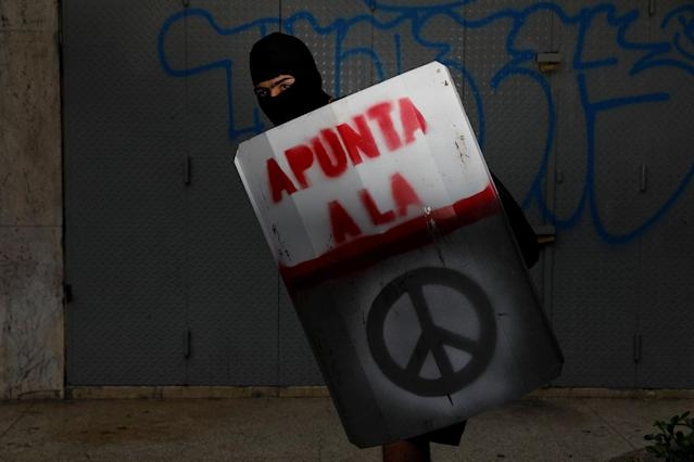 "<p>A demonstrator holding a rudimentary shield that reads ""Aim to the"", poses for a picture before a rally against Venezuelan President Nicolas Maduro's government in Caracas, Venezuela, June 17, 2017. He said: ""I protest to have a better Venezuela… Because today most of the young people graduate and have no chance of fulfilling their goals in the country. Venezuelans don't want any more dictatorship or repression, we want freedom."" (Photo: Carlos Garcia Rawlins/Reuters) </p>"