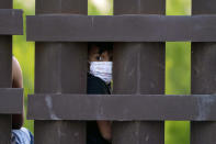 A migrant child looks through the U.S.-Mexico border wall as a group is processed and taken into custody while trying to sneak across the border, Sunday, March 21, 2021, in Abram-Perezville, Texas. (AP Photo/Julio Cortez)