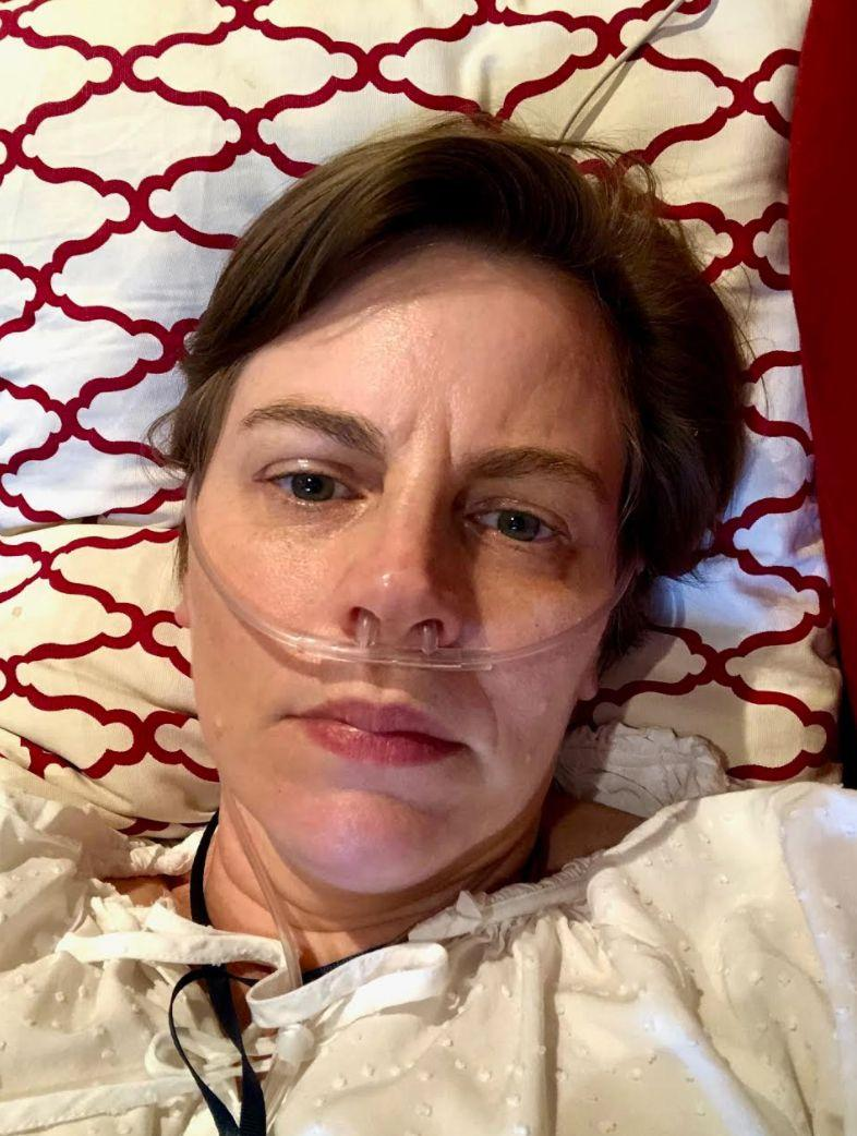 The author on her couch receiving oxygen in June 2020. (Photo: Courtesy of Ann E. Wallace)