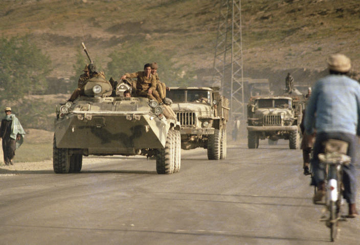 FILE - In this April 23, 1988 file photo, an Afghan cyclist passes by a Soviet military convoy led by an armored personnel carrier on the highway leading to Kabul The Soviet troops will begin its first phrase of withdrawal on May 15. Afghanistan is marking the 31st anniversary of the Soviet Union's last soldier leaving the country, Saturday, Feb. 15, 2020. This year's anniversary comes as the United States negotiates its own exit after 18 years of war, America's longest. (AP Photo/Liu Heung Shing, File)