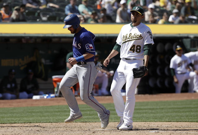 Texas Rangers' Jeff Mathis, left, scores a run past Oakland Athletics pitcher Joakim Soria (48) during the seventh inning of a baseball game in Oakland, Calif., Wednesday, April 24, 2019. (AP Photo/Jeff Chiu)
