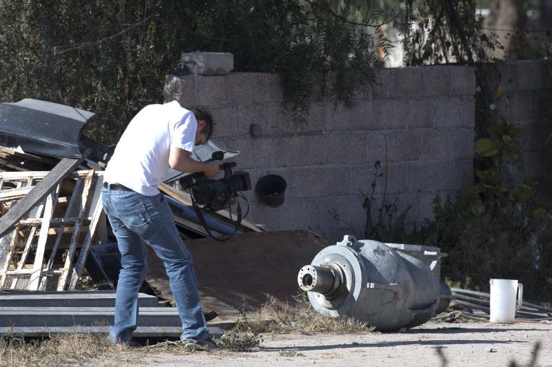 A cameraman films the radiation head that was part of a radiation therapy machine, in the patio of the family who found the stolen equipment abandoned in a nearby field, in the village of Hueypoxtla, Mexico, Friday, Dec. 6, 2013. The truck that was hauling the equipment was found abandoned Wednesday about 40 kilometers (24 miles) from where it was stolen, and the container for the radioactive material was found opened. Authorities continued to work on Friday at the site where the material was found to extract it safely. (AP Photo/Eduardo Verdugo)