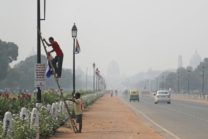 """India's Presidential Palace, in the backdrop, is covered with smog as a municipal worker removes flags from a light pole along Rajapth, the ceremonial boulevard in New Delhi, India, Wednesday, Oct. 16, 2019. The Indian capital's air quality levels have plunged to """"poor,"""" a day after the government initiated stricter measures to fight chronic air pollution. The state-run Central Pollution Control Board's air quality index for New Delhi stood at 299 on Wednesday, about six times the recommended level. (AP Photo/Altaf Qadri)"""