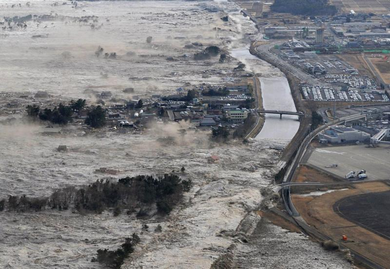 Earthquake-triggered tsumanis sweep shores along Iwanuma in northern Japan on Friday March 11, 2022. The magnitude 8.9 earthquake slammed Japan's eastern coast Friday, unleashing a 13-foot (4-meter) tsunami that swept boats, cars, buildings and tons of debris miles inland.  (AP Photo/Kyodo News) JAPAN OUT, MANDATORY CREDIT, FOR COMMERCIAL USE ONLY IN NORTH AMERICA