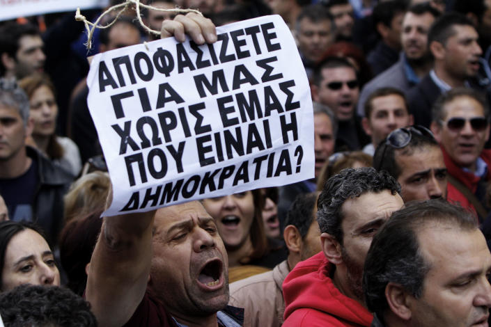 """A protestor holds a banner that reads in Greek """"You decide for us without us, where's the democracy in that?"""" outside of the Parliament during a strike to protest government plans to privatize state-run organizations in Nicosia, Cyprus, Thursday, Feb. 27, 2014. Hundreds of protesters have gathered outside Cyprus' parliament to voice opposition against legislation that will pave the way for the privatization of state-owned companies. (AP Photo/Petros Karadjias)"""