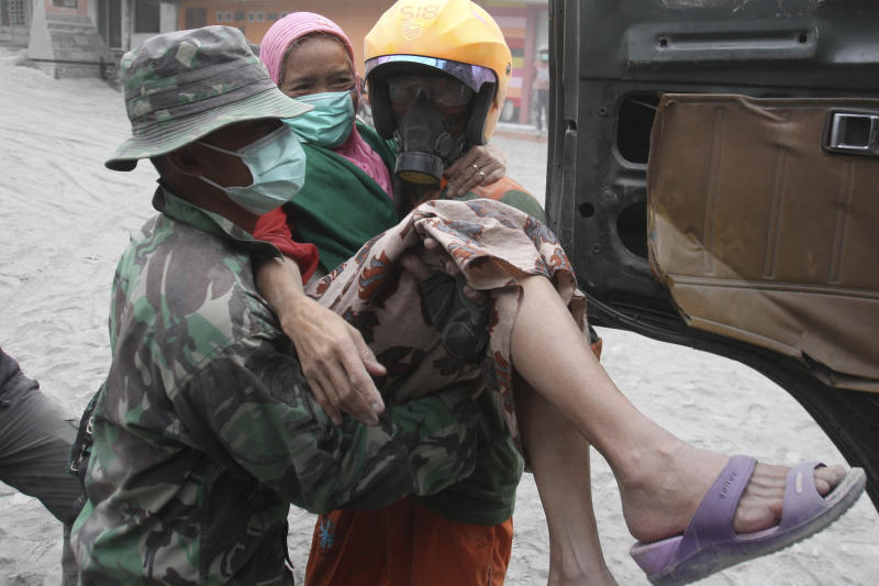 Soldiers and rescuers carry a woman to a truck for evacuation following an eruption of Mount Kelud, in Malang, East Java, Indonesia, Saturday, Feb. 15, 2014. The powerful volcanic eruption on Indonesia's most populous island blasted ash and debris 18 kilometers (12 miles) into the air Friday, forcing authorities to evacuate more than 100,000 and close seven airports. (AP Photo/Trisnadi)