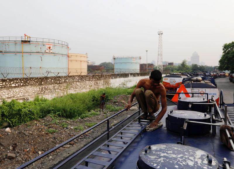 A man cleans an oil tanker parked outside a Hindustan Petroleum fuel depot in Mumbai
