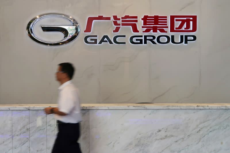 Man walks past the logo of Chinese automobile maker GAC Group at the company headquarters in Guangzhou