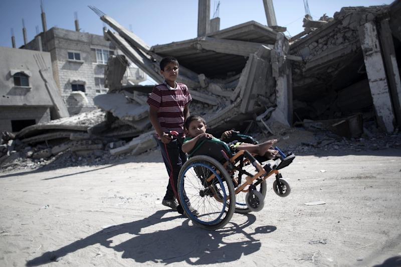 A Palestinian boy pushes the wheelchair of his brother, injured during the 50-day war between Israel and Hamas militants in the summer of 2014, on July 29, 2015 in Rafah (AFP Photo/Said Khatib)