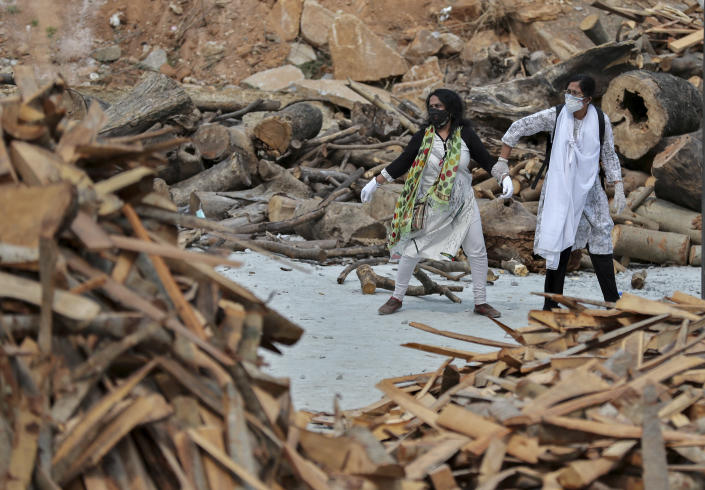 A woman pulls away her crying relative as she reacts to the burning funeral pyre of their family member who died of COVID-19, at an open crematorium set up at a granite quarry on the outskirts of Bengaluru, India, Wednesday, May 5, 2021. (AP Photo/Aijaz Rahi)