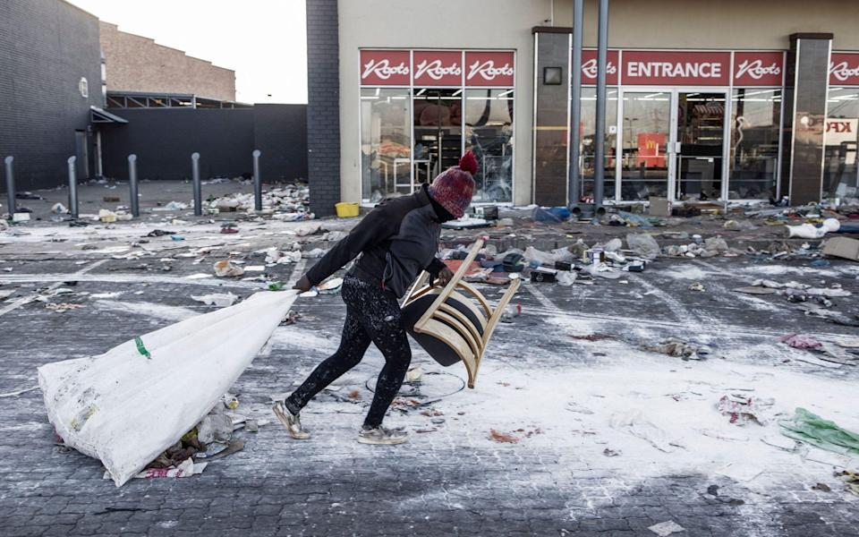 A suspected looter pulls a sack along the ground outside a vandalised mall in Vosloorus, on the outskirts of Johannesburg - MARCO LONGARI /AFP