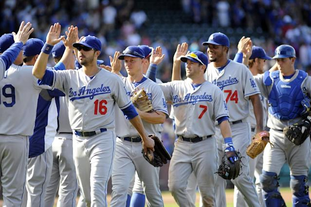 Los Angeles Dodgers players high-five each other after their 1-0 victory over the Chicago Cubs in a baseball game, Sunday, Aug. 4, 2013, in Chicago. (AP Photo/Joe Raymond)