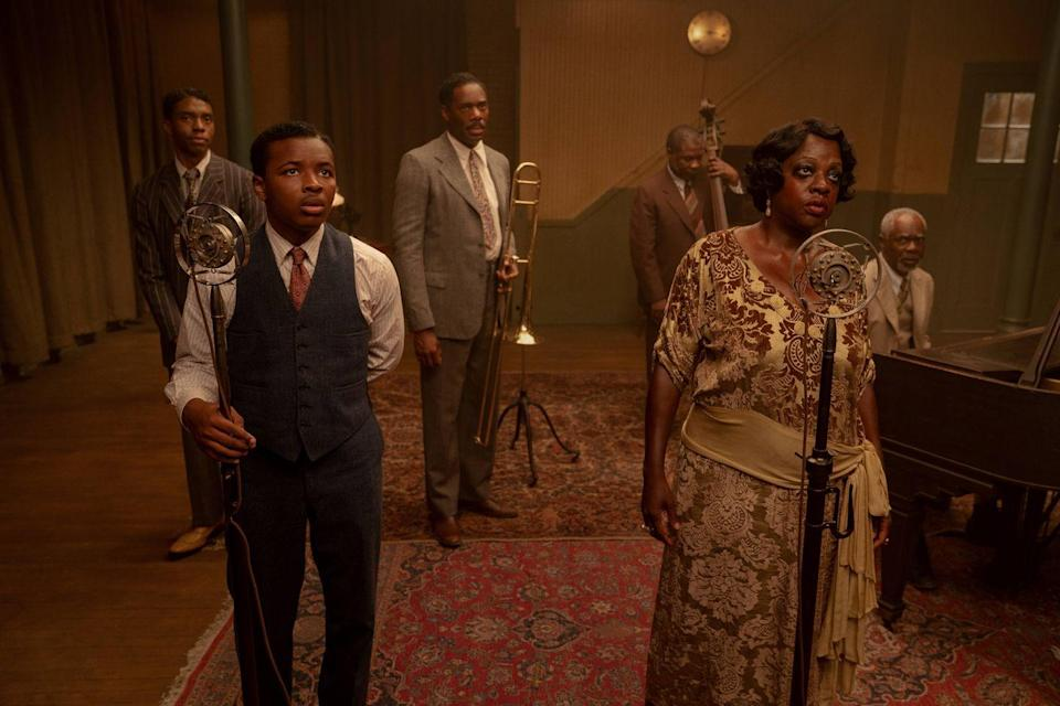 """<p><strong>Production design by Mark Ricker; set decoration by Karen O'Hara and Diana Stoughton.</strong><br><br>Although George C. Wolfe's adaptation of August Wilson's 1982 play <em>Ma Rainey's Black Bottom</em> is a vignette of the music scene of the Roaring '20s, glitz and glamour are far from what Ma Rainey (Viola Davis), ''Queen of the Blues,'' and her band (Chadwick Boseman, Coleman Domingo, Michael Potts, and Glynn Turman) experience in Chicago, as the singer fights for control over her music in a time of racial prejudices and injustices. </p><p>The film is set in Chicago but was actually filmed in Wilson's hometown of Pittsburgh, so production designer Mark Ricker had some studying to do to get all the details of a 1920s-era Windy City right and ready for action. </p><p>Ricker was able to find the perfect location for the recording studio fitting Wolfe's description: """"a fantastic small vaudeville Victorian theater,"""" according to production notes. Unfortunately, a few days before shooting, that location fell through, so Ricker and his team built a studio on a soundstage. In the end the mishap worked in their favor, as they were able to add details that they wouldn't have in the other location.</p><p>A huge part of the film was the claustrophobic atmosphere and heat the characters were feeling (indoors and outdoors) that, in turn, would make viewers uncomfortable. The design of a basement rehearsal room was especially crucial. Although Wolfe pictured a windowless room, Ricker and the cinematographer, Tobias Schliessler, decided to add one window to display the source of the heat and add a temporal quality. """"We were literally going to track the light moving over the course of the film, and we're very cognizant of the light as it pertains to the heat on this hot day in July in Chicago in 1927,"""" Ricker noted.</p>"""