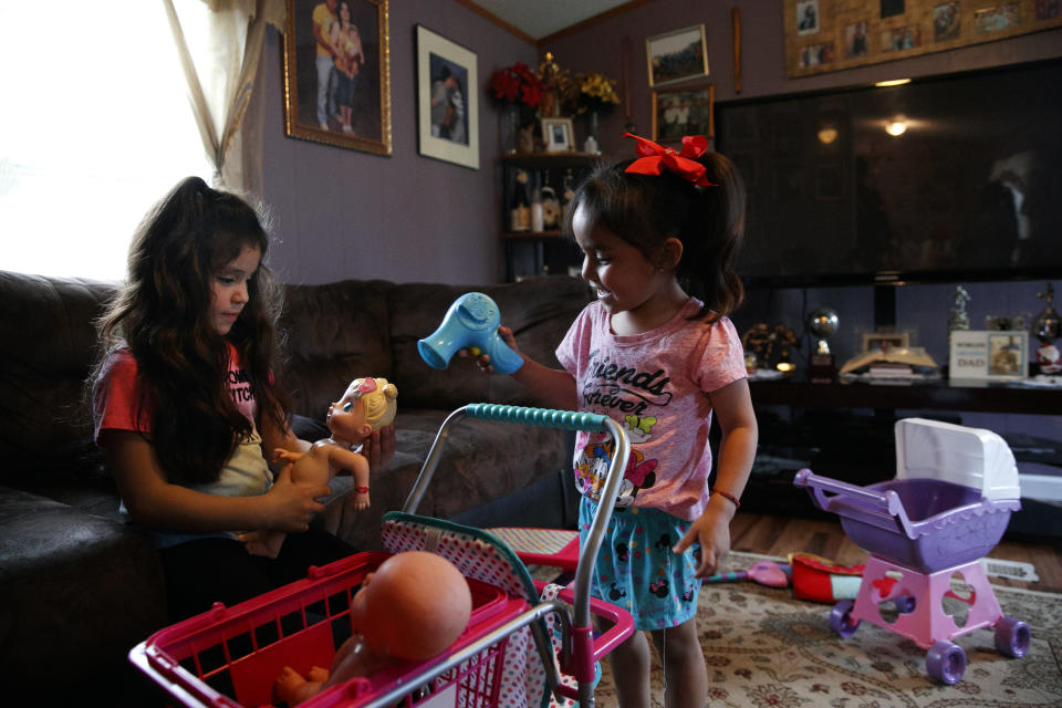 Alexa Montoya, 5, left, and Kimberly Rivera, 3, play with dolls as Kimberly's mother registers to vote during a voter registration in a largely Latino trailer community in Burlington, N.C., Wednesday, March 11, 2020. (AP Photo/Jacquelyn Martin)