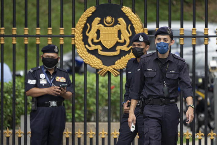 Police officers wearing face masks guard outside National Palace in Kuala Lumpur, Malaysia, Thursday, June 10, 2021. (AP Photo/Vincent Thian)