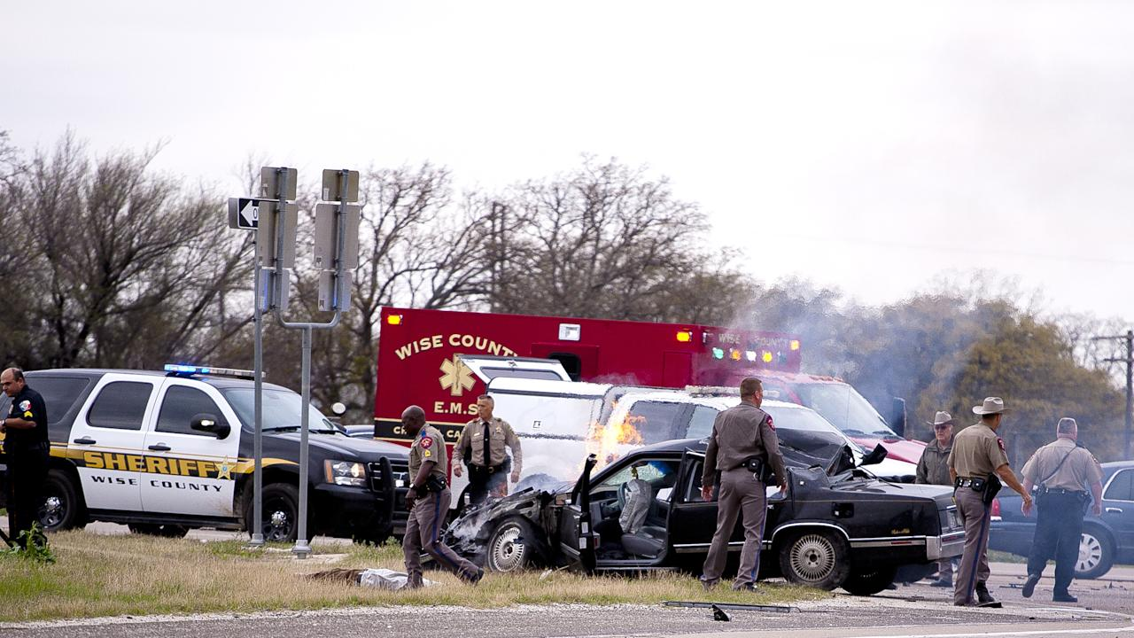 Emergency personnel are on the scene of a crash and shootout with police involving the driver of a black Cadillac with Colorado plates in Decatur, Texas, Thursday, March 21, 2013. The driver led police on a gunfire-filled chase through rural Montague County, crashed his car into a truck in Decatur, opened fire on authorities and was shot, officials said. Texas authorities are checking whether the Cadillac is the same car spotted near the home of Colorado prisons chief Tom Clements, who was shot and killed when he answered the door Tuesday night. (AP Photo/Wise County Messenger, Jimmy Alford) MANDATORY CREDIT, MAGS OUT
