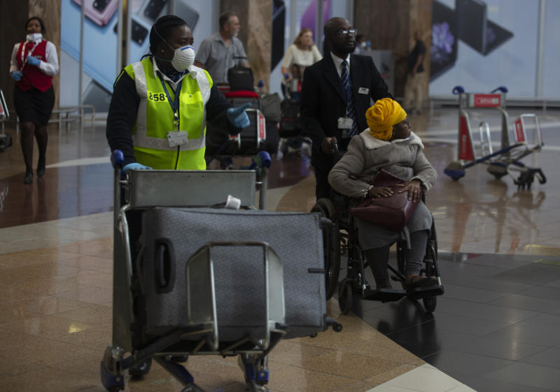 An elderly passenger arrives in a wheelchair at Johannesburg's O.R. Tambo International Airport, Monday, March 16, 2020, a day after President Cyril Ramaphosa declared a national state of disaster. Ramaphosa said all schools will be closed for 30 days from Wednesday and he banned all public gatherings of more than 100 people. South Africa will close 35 of its 53 land borders and will intensify screening at its international airports. For most people, the new COVID-19 coronavirus causes only mild or moderate symptoms. For some it can cause more severe illness. (AP Photo/Denis Farrell)