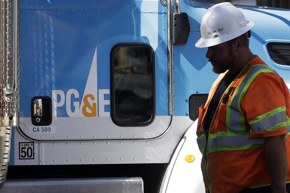 FILE - In this Aug. 15, 2019, file photo, a Pacific Gas & Electric worker walks in front of a truck in San Francisco. PG&E's household customers will be hit with an average rate increase of 8% to help the once-bankrupt utility pay for improvements designed to reduce the risks that its outdated equipment will ignite deadly wildfires in its Northern California service territory. The higher prices, effective March 1, are expected to boost the bills of PG&E's residential customers by an average of $13.44 to per month. (AP Photo/Jeff Chiu, File)