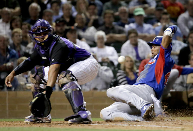 Chicago Cubs' Emilio Bonifacio, right, scores past Colorado Rockies catcher Wilin Rosario on a double by Darwin Barney during the fifth inning of a spring exhibition baseball game in Scottsdale, Ariz., Wednesday, March 19, 2014. (AP Photo/Chris Carlson)