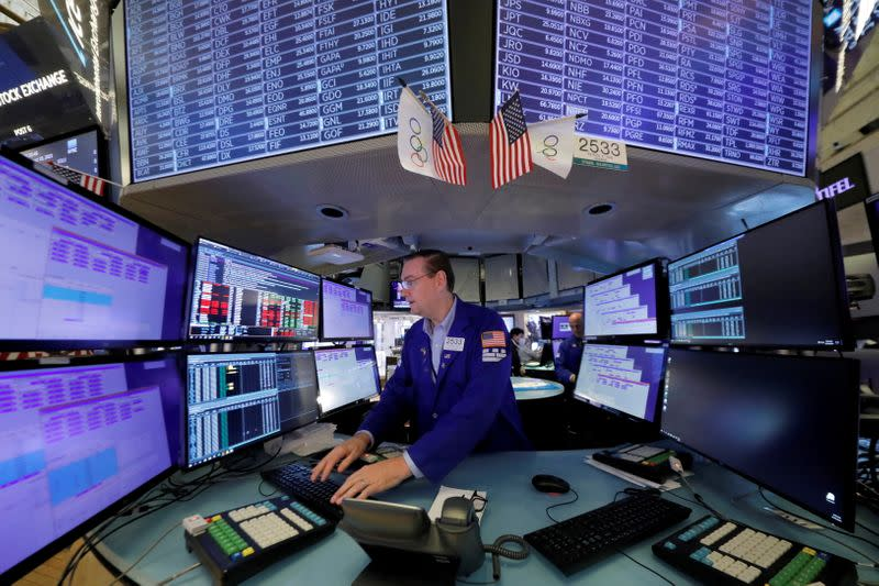 FILE PHOTO: A trader works at the New York Stock Exchange (NYSE) in Manhattan, New York City