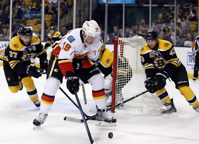 Calgary Flames center Blair Jones (19) tries to control the puck as Boston Bruins center Patrice Bergeron (37) and defenseman Matt Bartkowski (43) close in to defend during the first period of an NHL hockey game in Boston, Tuesday, Dec. 17, 2013. (AP Photo/Elise Amendola)