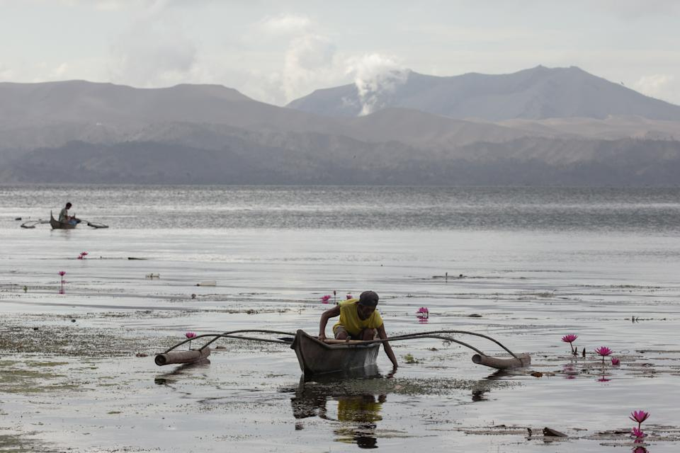 FILE PHOTO: A man catches fish as Taal Volcano spews ash in Talisay, Batangas on January 20, 2020. (Source: REUTERS/Eloisa Lopez)