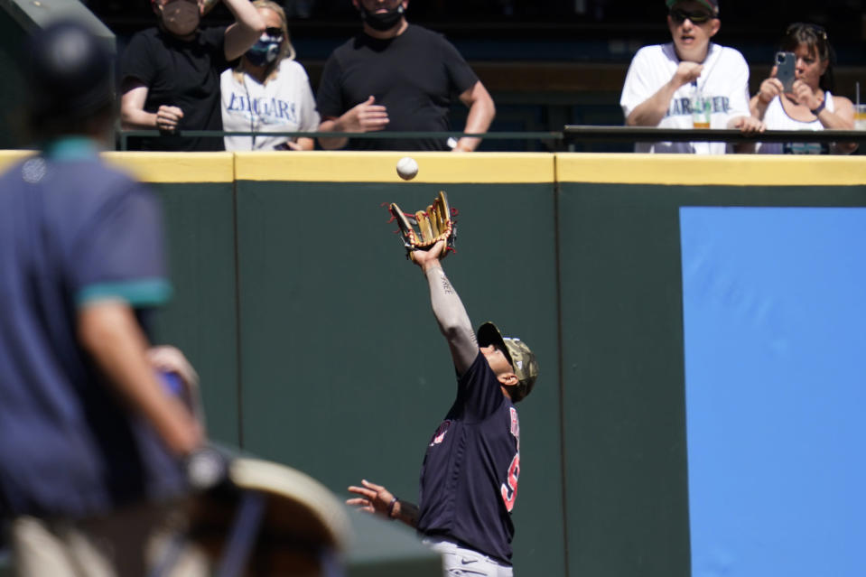 Cleveland Indians left fielder Eddie Rosario snags a fly ball deep into the corner for an out in the first inning of a baseball game Sunday, May 16, 2021, in Seattle. (AP Photo/Elaine Thompson)