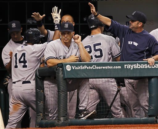 New York Yankees' Curtis Granderson (14) and Mark Teixeira (25) are congratulated behind manager Joe Girardi, center, after scoring during the eighth inning of a baseball game against the Tampa Bay Rays,Wednesday, July 4, 2012, in St. Petersburg, Fla. The Yankees won 4-3. (AP Photo/Mike Carlson)