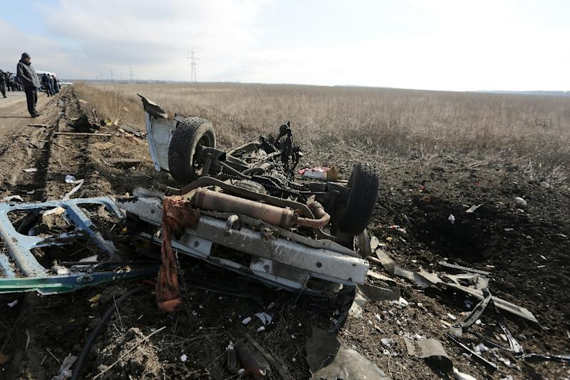 People look at the debris of a passenger minibus after it hit a mine as they queue to cross the demarcation line between territory controlled by pro-Russian separatists and Ukrainian territory near Marinka on February 10, 2016