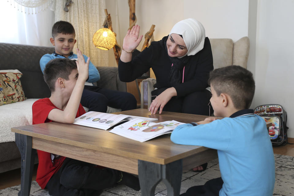 """Fatima Alzahra Shon, 32, a Syrian refugee, teaches her children after an interview with The Associated Press in Istanbul, Friday, Sept. 17, 2021. Shon thinks neighbors attacked her and her son Amr, top left, in their Istanbul apartment building because she is Syrian. The 32-year-old refugee from Aleppo was confronted on Sept. 1 by a Turkish woman who asked her what she was doing in """"our"""" country. Shon replied, """"Who are you to say that to me?"""" The situation quickly escalated. (AP Photo/Emrah Gurel)"""