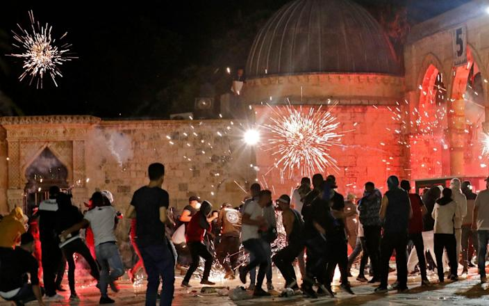 Stun grenades burst in the air amid clashes between Palestinian protesters and Israeli security forces at the al-Aqsa mosque compound in Jerusalem - AFP/AFP