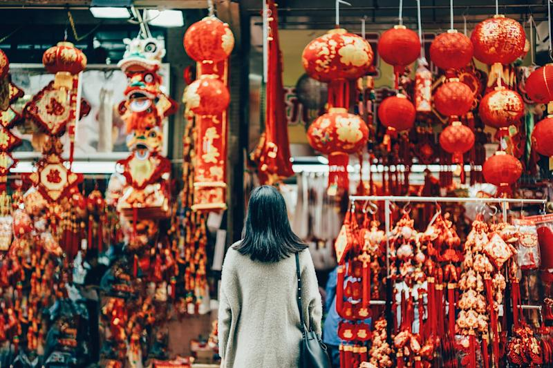 Rear view of woman standing against various Chinese New Year decorations and ornaments on city street