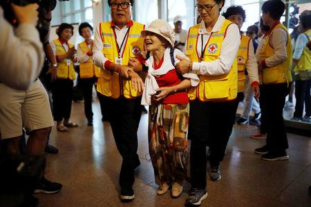 Lee Geum-seom, who has been selected as a participant for a reunion, is helped by volunteers as she arrives at a hotel used as a waiting place in Sokcho, South Korea, August 19, 2018.    REUTERS/Kim Hong-Ji
