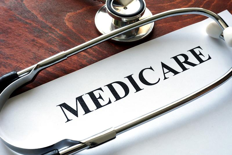 """Paper titled """"Medicare"""" with a stethoscope, both on a wood table."""