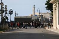 Plain clothes police block a road during a protest against and in support of the government in Havana