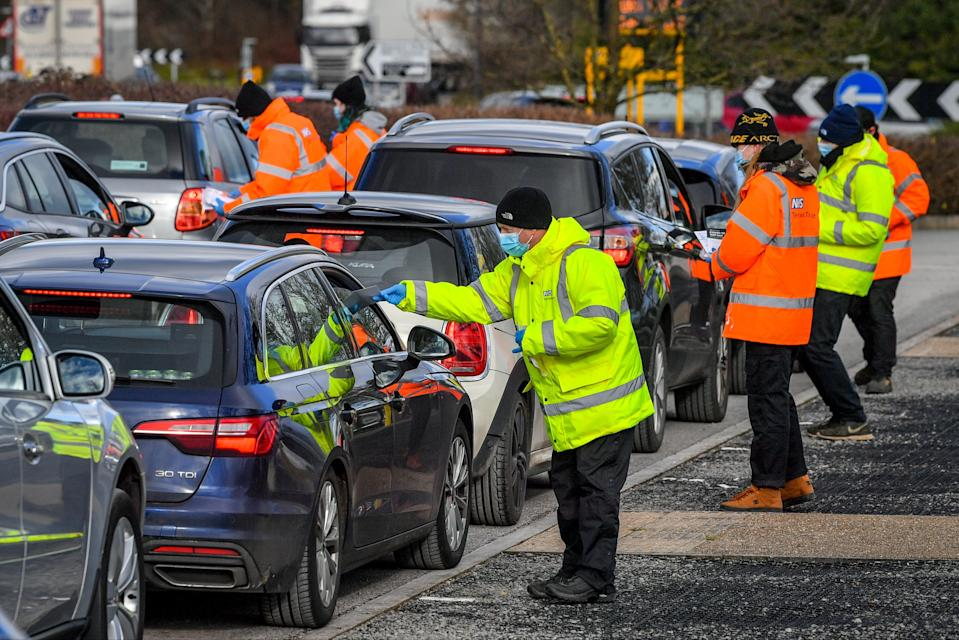 Testing staff hand out kits to motorists attending a surge testing centre at the Science Park, Emersons Green, in Bristol, Gloucestershire (PA)