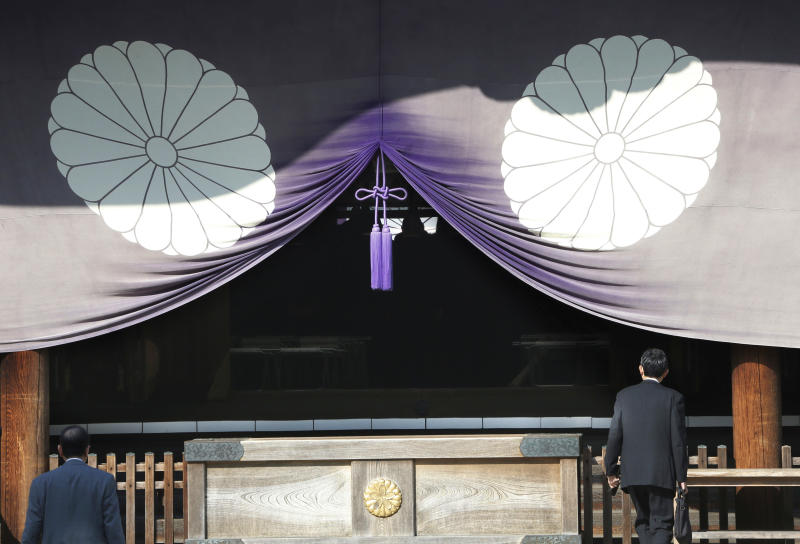 FILE - In this April 23, 2013 file photo, a group of Japanese lawmakers, seen silhouetted in the middle of the photo, offer prayers at the Yasukuni Shrine, which honors Japan's war dead, including World War II leaders convicted of war crimes, in Tokyo during an annual spring festival. A Japanese Cabinet minister visited the Tokyo shrine that honors the dead including war criminals in what has repeatedly caused friction with Japan's neighbors. Lawmaker Keiji Furuya, who chairs the National Public Safety Commission, said on his website that he paid respects Sunday morning, April 20, 2014, at the Yasukuni shrine ahead of a festival that starts Monday.(AP Photo/Koji Sasahara, File)