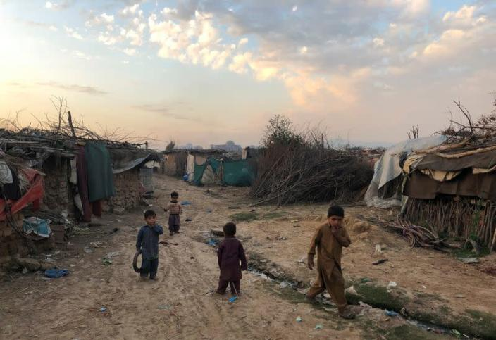 Children play outside their family's shelters at Afghan refugee camp in Islamabad
