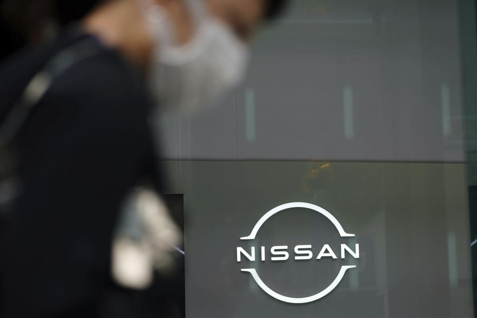 A man wearing a face mask to to help curb the spread of the coronavirus walks by the logo of Nissan seen at the automaker's showroom in Tokyo Tuesday, May 11, 2021. Nissan reduced its losses for January-March, compared to last year, as restructuring efforts kicked in, despite the sales damage from the coronavirus pandemic, the Japanese automaker said Tuesday. (AP Photo/Eugene Hoshiko)
