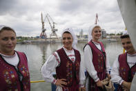Folk dancers stand during a ceremony marking 100 years of diplomatic relations between Japan and Romania, at the construction site of a suspension bridge over the Danube river in Braila, Romania, Thursday, Aug. 26, 2021. The bridge, built by Japanese and Italian companies, with a span of 1,974.3 meters, will be the largest of its kind in Romania and the third in the European union.(AP Photo/Vadim Ghirda)